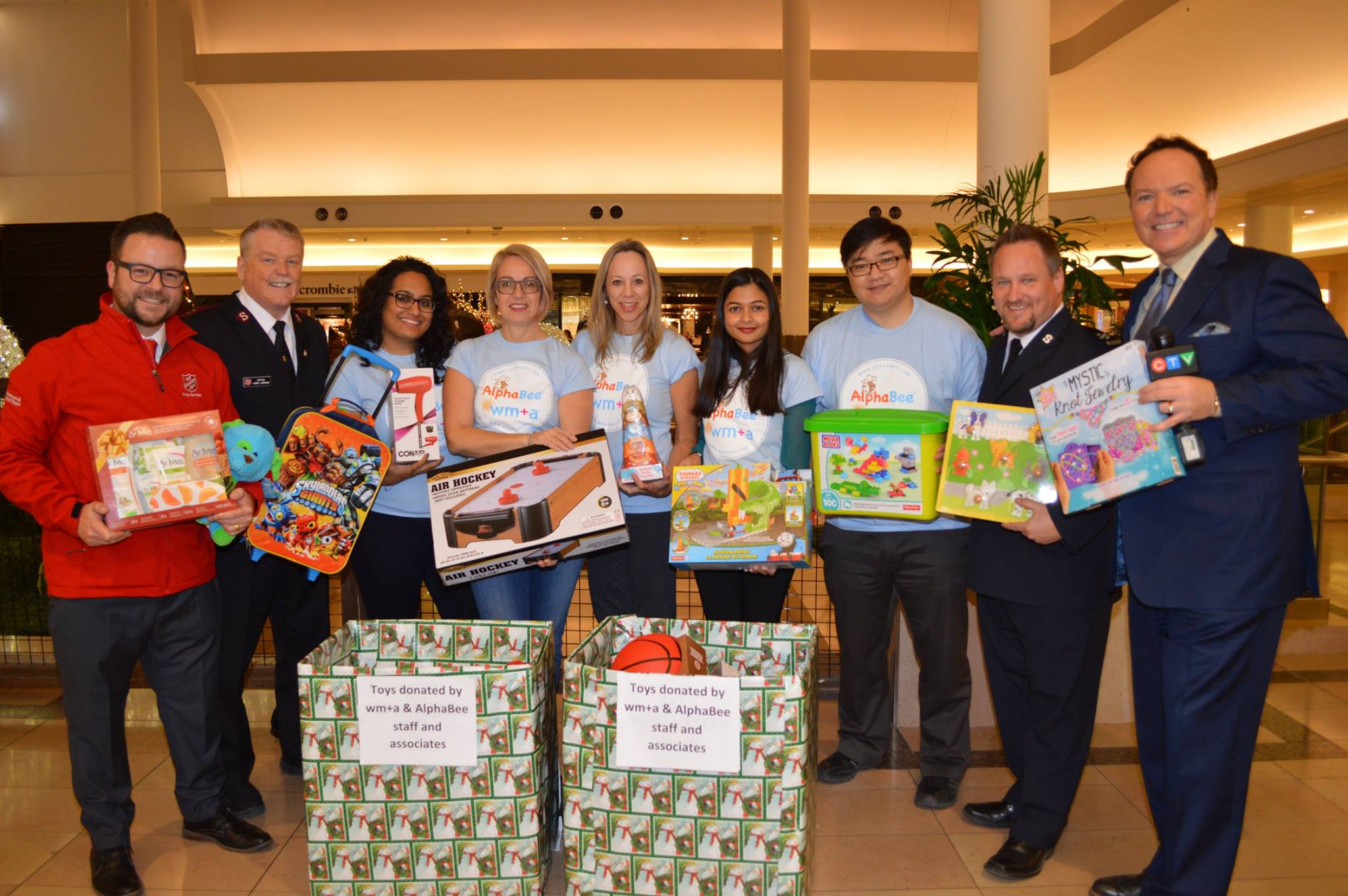 wm+a and AlphaBee staff show off the toys donated for the Salvation Army with reporters from CTV